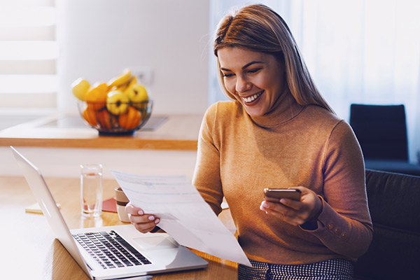 woman in sweater holding bills in one hand and in other smart phone