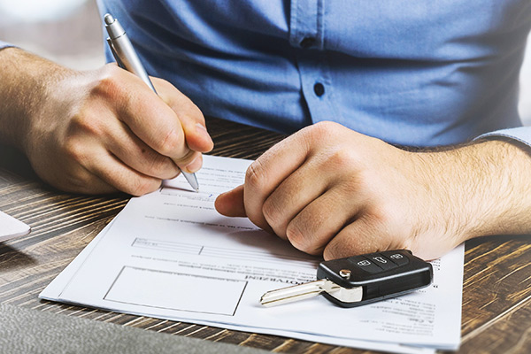 Man signing car document or lease paper